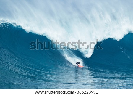 """MAUI, HI - JANUARY 16 2016: Professional surfer Will Hunt rides a giant wave at the legendary big wave surf break known as """"Jaws"""" on one the largest swells of the year. - stock photo"""