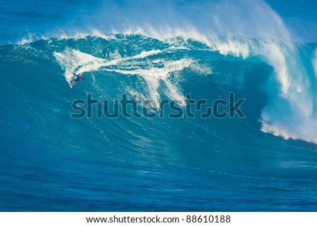 """MAUI, HI - MARCH 13: Professional surfer Archie Kalepa rides a giant wave at the legendary big wave surf break known as """"Jaws"""" during one the largest swells of the winter March 13, 2011 in Maui, HI. - stock photo"""