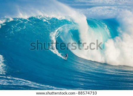 """MAUI, HI - MARCH 13: Professional surfer Billy Kemper catches a giant wave at the legendary big wave surf break known as """"Jaws"""" during one the largest swells of the winter March 13, 2011 in Maui, HI. - stock photo"""