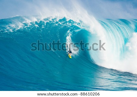 """MAUI, HI - MARCH 13: Professional surfer Carlos Burle rides a giant wave at the legendary big wave surf break known as """"Jaws"""" during one the largest swells of the winter March 13, 2011 in Maui, HI. - stock photo"""