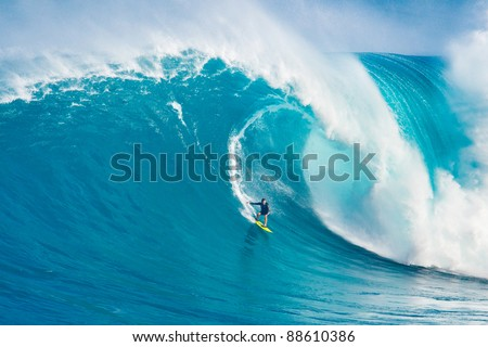 """MAUI, HI - MARCH 13: Professional surfer Carlos Burle rides a giant wave at the legendary big wave surf break """"Jaws"""" during one the largest swells of the winter March 13, 2011 in Maui, HI. - stock photo"""