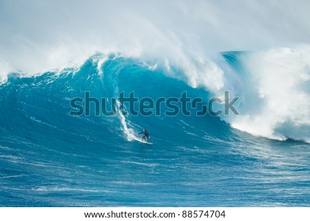 """MAUI, HI - MARCH 13: Professional surfer Hanu Sandru rides a giant wave at the legendary big wave surf break known as """"Jaws"""" during one the largest swells of the winter March 13, 2011 in Maui, HI. - stock photo"""