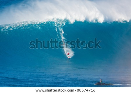 """MAUI, HI - MARCH 13: Professional surfer Kiva Rivers catches a giant wave at the legendary big wave surf break known as """"Jaws"""" during one the largest swells of the winter March 13, 2011 in Maui, HI. - stock photo"""