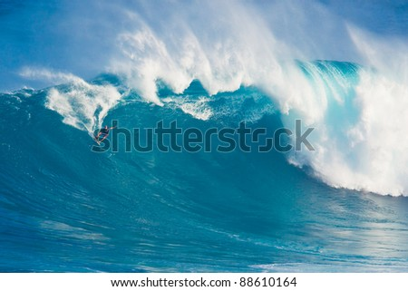 """MAUI, HI - MARCH 13: Professional surfer Laird Hamilton rides a giant wave at the legendary big wave surf break known as """"Jaws"""" during one the largest swells of the winter March 13, 2011 in Maui, HI. - stock photo"""