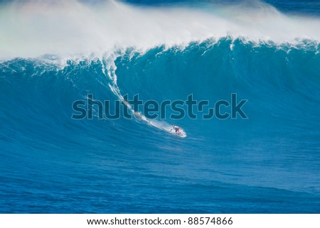 """MAUI, HI - MARCH 13: Professional surfer Michel Larronde rides a giant wave at the legendary big wave surf break known as """"Jaws"""" during one the largest swells of the winter March 13, 2011 in Maui, HI. - stock photo"""