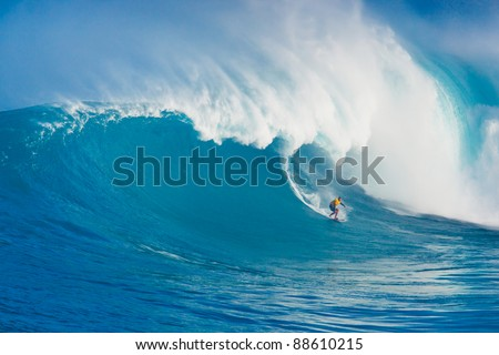 """MAUI, HI - MARCH 13: Professional surfer Yuri Soledade rides a giant wave at the legendary big wave surf break known as """"Jaws"""" during one the largest swells of the winter March 13, 2011 in Maui, HI. - stock photo"""