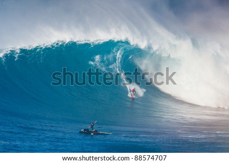 """MAUI, HI - MARCHh 13: Professional surfer Yuri Soledade rides a giant wave at the legendary big wave surf break known as """"Jaws"""" during one the largest swells of the winter March 13, 2011 in Maui, HI. - stock photo"""