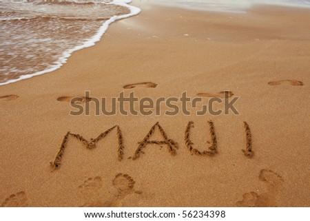 maui written in the sand on the hawaiian beach - stock photo