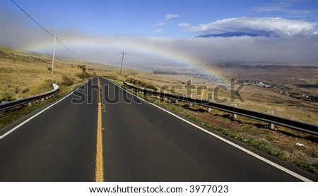 Mauna Loa looms in the distance as rain clouds and a rainbow decorate the road from Hawi to Waimea on the Big Island of Hawaii. - stock photo