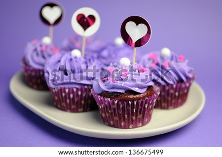 Mauve purple decorated cupcakes for children or teens birthday, or bachelorette, bridal or baby shower party function. Closeup with bokeh. - stock photo