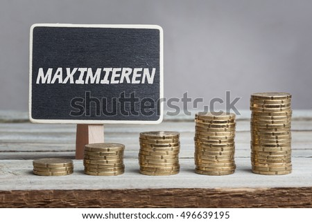 Maximieren (maximize) in German language, white chalk type on black board, Euro money coin stacks of growth on wood table.