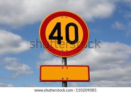 Maximum speed 40 km per hour and blank letter plate for your text, with blue sky and clouds as background. - stock photo