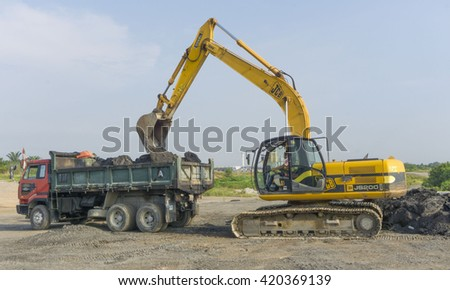 May 14, 2016 - Kuala Lumpur, Malaysia : A close-up of ayellow excavator on a construction site against blue sky.  - stock photo