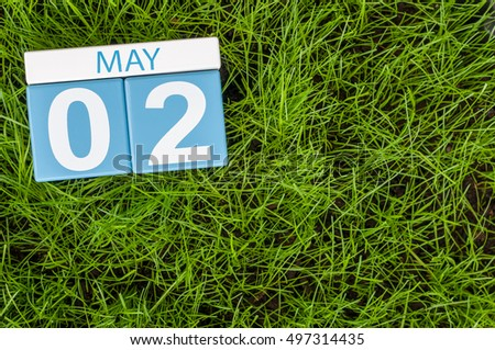 May 2nd. Day 2 of month, calendar on football green grass background. Spring time, empty space for text