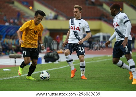 May 27, 2015 - Shah Alam, Malaysia: Malaysia's Joseph Kalang (17) takes on two Tottenham Hotspur defenders (white jersey) in a friendly match. Tottenham Hotspur is on a Asia-Australia tour. - stock photo
