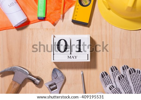 May 1st. Image of may 1 white blocks wooden calendar with construction tools on the table. International Workers' Day. Labor day concept. - stock photo