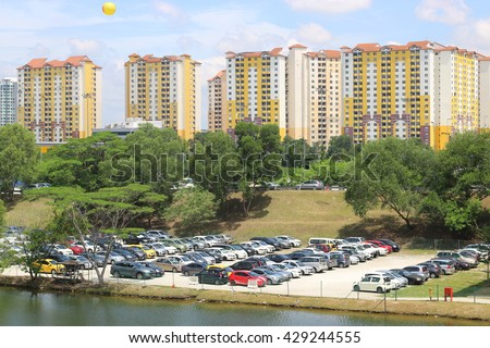 May 31, 2016, Subang Jaya, Selangor, Malaysia.  Cars parked in a public car park near a lake against a backdrop of trees and apartment units in an urban area.