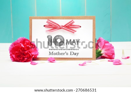 May 10th Mothers Day card with pink carnations over teal wooden background - stock photo