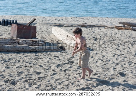 MAY 15TH 2015, Seattle: a boy playing on the Alki beach in a sunny day, Seattle WA - stock photo