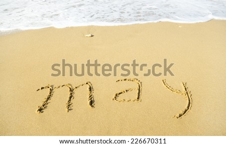 May - written in sand on beach texture - soft wave of the sea
