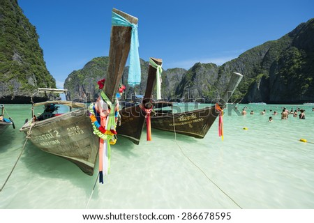 MAYA BAY, THAILAND - NOVEMBER 12, 2014: Traditional Thai longtail boats float in the foreground while visitors enjoy the turquoise waters of the popular Maya Bay. - stock photo