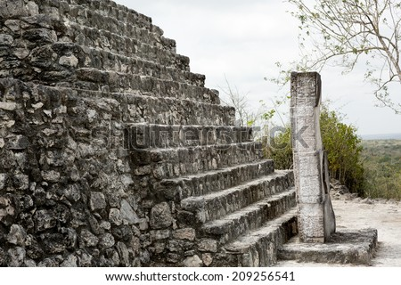 mayan building stairs details with a stela in front - stock photo