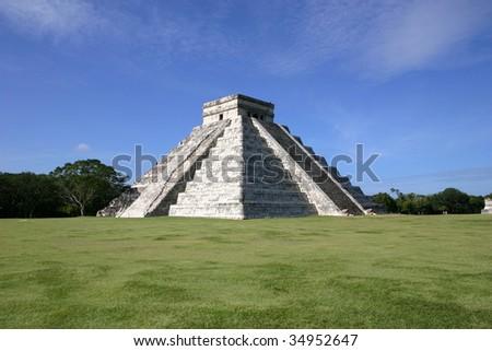 Mayan pyramid of El Castillo, between green field and blue sky: Chichen Itza, Mexico - stock photo