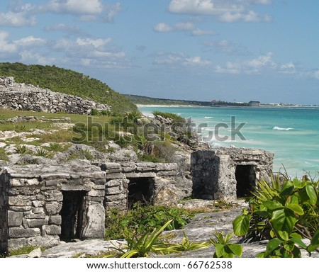Mayan ruins at Tulum on the Mexican coast near Cancun.  Note the tourist beaches and hotels in the background - stock photo