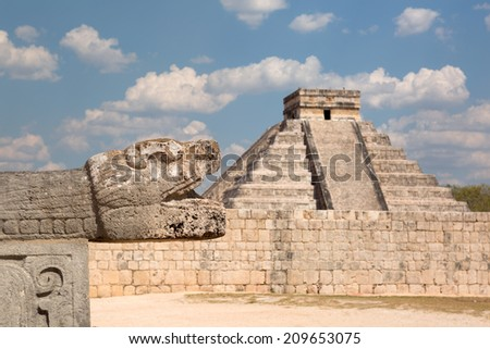Mayan stone snake head sculpture with the pyramid of Kukulcan in the background - stock photo