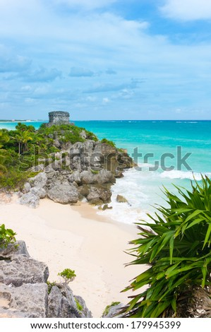 Mayan temple of God of winds on the beautiful empty Caribbean beach in Tulum (vertical). Picturesque view of turquoise water of Caribbean sea, white sand, tropical palms and blue sky - stock photo