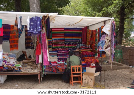 Mayan Woman in a Market Booth with Colorful Textiles - stock photo