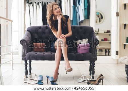 Maybe I need another pair? Beautiful young woman looking thoughtful while sitting on sofa at the clothing store - stock photo
