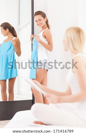 Maybe this dress? Beautiful young woman standing near the mirror with blue dress and looking at another women sitting on the foreground with magazine - stock photo