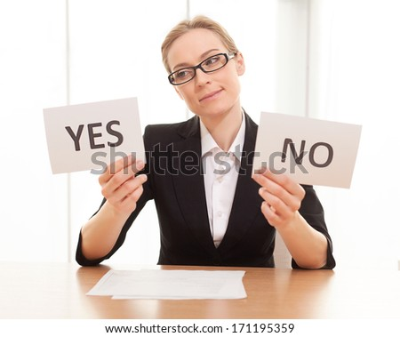 Maybe yes? Thoughtful mature woman in formalwear sitting at the table and holding papers with yes and no on them - stock photo
