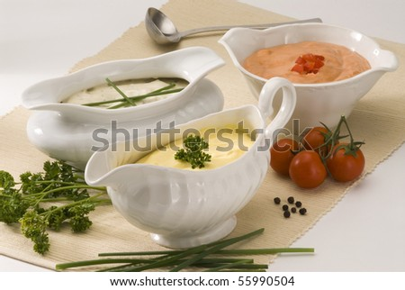 Mayonnaise cheese and cocktail sauces in sauce-boats. Salad dressing. - stock photo