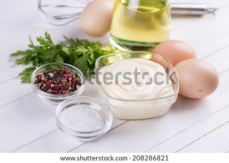 Mayonnaise in bowl and ingredients for it. Selective focus. - stock photo