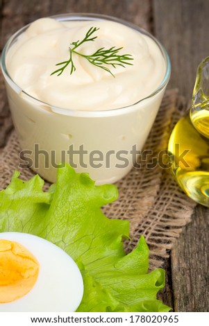 Mayonnaise in bowl with egg and lettuce - stock photo