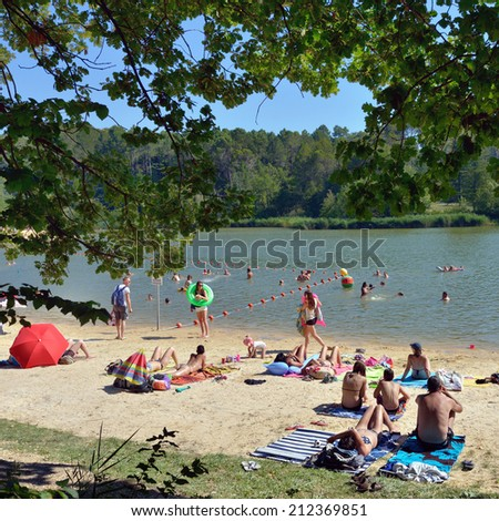 MAZAN, FRANCE - JUL 19, 2014: People have a rest on the shore of lake in southern France, Provence. A  lot of small lakes is a popular recreation areas for local people to avoid summer heat - stock photo