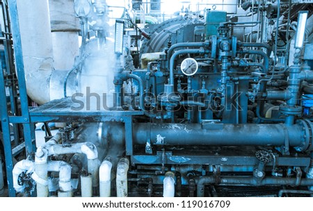 Maze of Pipes and Valves Inside Industrial Facility - stock photo