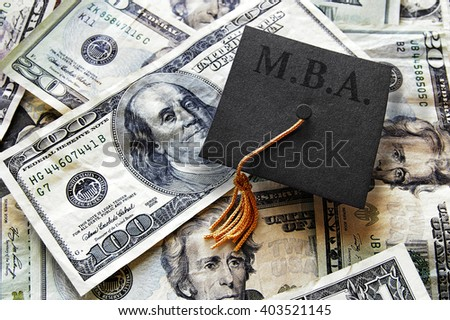 MBA graduation cap on hundred dollar bills -- Masters of Business Administration concept                                - stock photo
