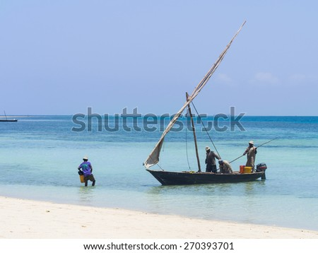 MBUDYA ISLAND, TANZANIA: MARCH 08, 2015: Tanzanian fishermen on a dhow boat on the beach on Mbudya Island in Tanzania, close to Dar es Salaam, working on a Sunday afternoon. Landscape orientation. - stock photo