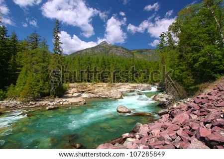 McDonald Creek flows swiftly through the forests of Glacier National Park in Montana - stock photo
