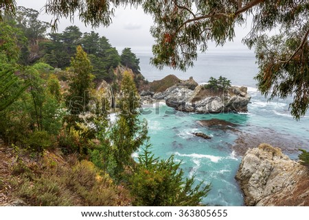 McWay Falls at Julia Pfeiffer Burns State Park, with aquamarine seas, along a rocky coastline, covered with trees. Traveling the Big Sur Highway (Highway 1) on the California Central Coast. - stock photo