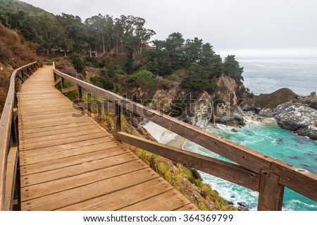 McWay Falls connector bridge at Julia Pfeiffer Burns State Park, with aquamarine seas, along a rocky coastline, covered with trees. Traveling the Big Sur Highway, on the California Central Coast. - stock photo