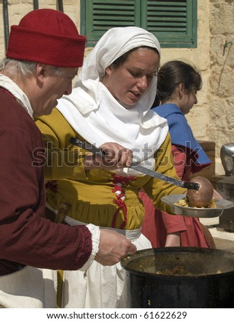 MDINA, MALTA - APR10:  Woman preparing traditional food during medieval reenactment in the old city of Mdina in Malta April 10, 2010