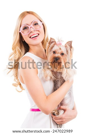 Me and my glamorous friend. Beautiful young blond hair woman carrying Yorkshire terrier in pink clothes and smiling while standing isolated on white background