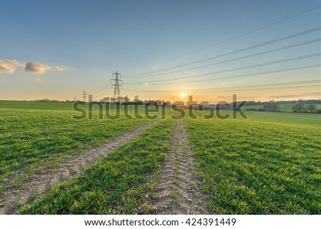 Meadow and Electricity Pylon - UK standard overhead power line transmission tower at sunset - stock photo