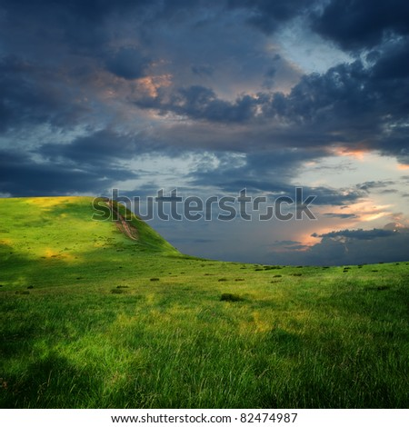 meadow and majestic sky with  clouds over the green hills - stock photo