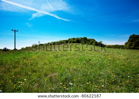 meadow and power line against the blue sky - stock photo
