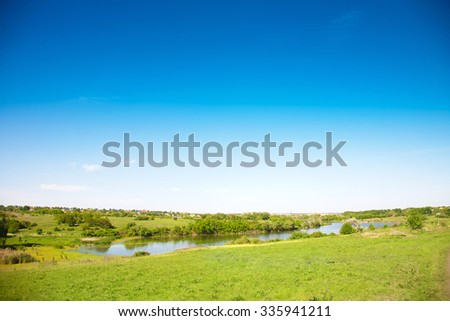 Meadow and valley with a pond on a sunny summer day - stock photo